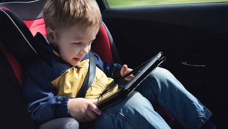 ребенок играет на планшете в дороге